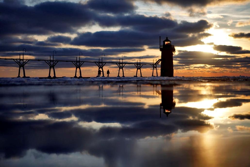 A lemenő nap fénye és a déli móló világítótornyának képe tükröződik a Michigan-tó vizében a Michigan állambeli South Havenben 2009. december 29-én.