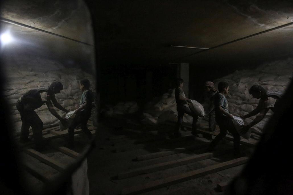 mti.17.05.03. Humanitárius segélyszállítmányt rakodnak egy föld alatti óvóhelyen a szíriai főváros, Damaszkusz közelében fekvő Dumában 2017. május 2-án, miután az ENSZ, a Szíriai Vörös Félhold és a Vöröskereszt Nemzetközi Bizottságának (ICRC) tartós élelm