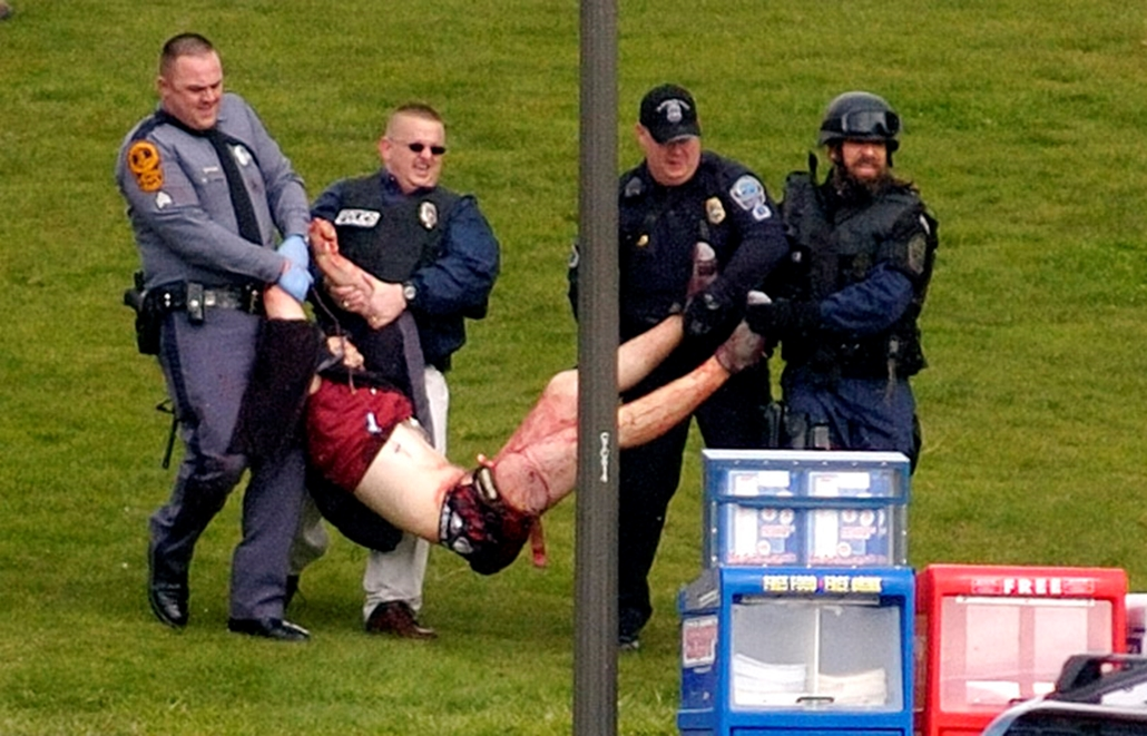 Rendőrök egy túlélőt visznek biztos helyre, miután egy ámokfutó 33 embert ölt meg az Egyesült Államok történetének legvéresebb iskolai mészárlásban a Virginia Tech egyetemen 2007. április 16-án.