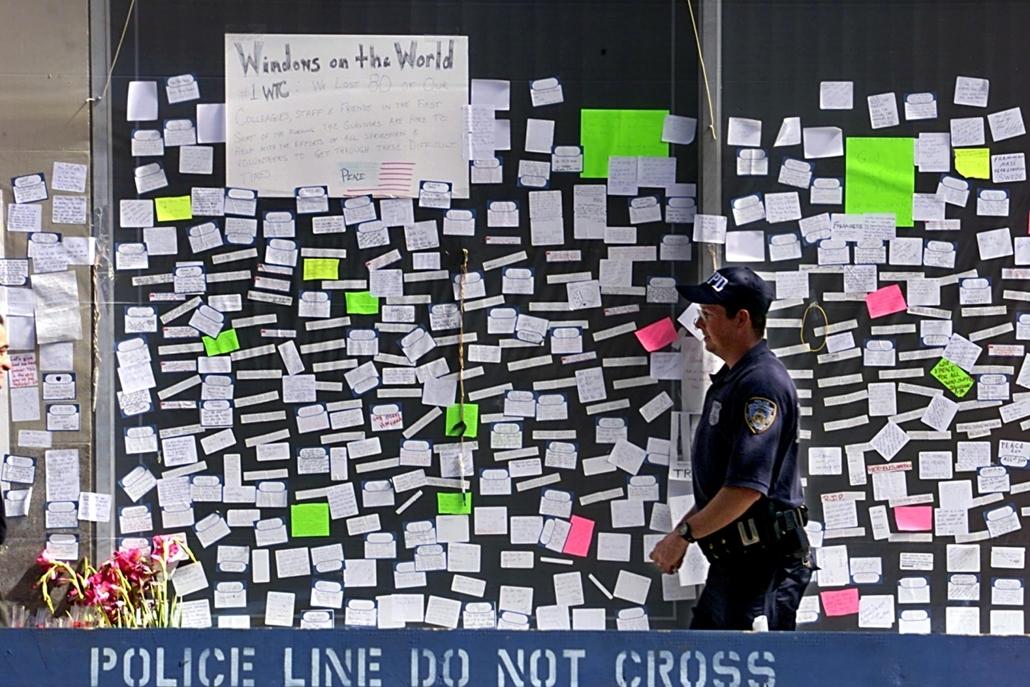 afp.01.09.19. Egy New York-i rendőr egy ablak előtt sétál el szeptember 19-én, amelyet a terrortámadás áldozatainak nevei borítanak be .
