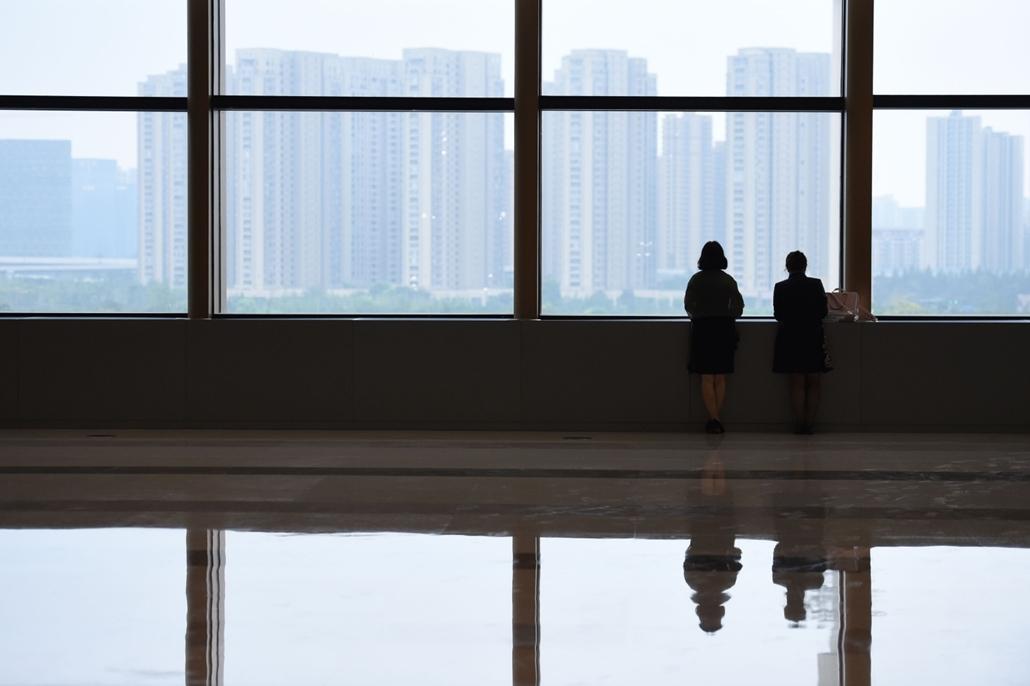 afp.16.09.02. Két nő néz ki az ablakon Hangzhou-ban, Kína egyik városában.