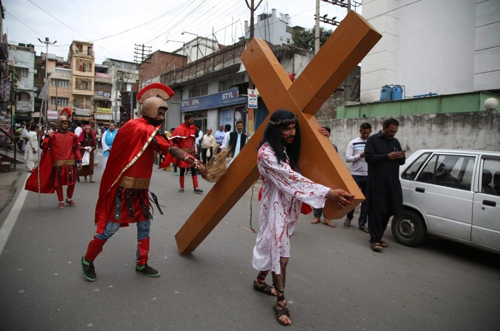 epa.16.03.25. - Dzsammu, India: Indiai keresztény fakereszttel, mialatt egy római katonának öltözött társa jelképesen ostorozza a Jézus Krisztus keresztútját felidéző hagyományos nagypénteki kálváriajáráson. - húsvét, nagyítás