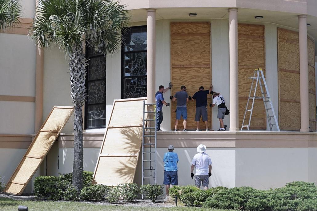 AP!!! mti.19.08.30. Dorian hurrikán A munkások bedeszkázzák a Santa Maria del Mar katolikus templom ablakait a floridai Flagler Beach településen 2019. augusztus 30-án