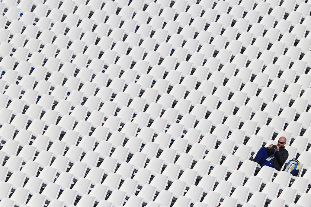 afp. Szocsi 2014 nagyítás - A man sits on the tribune after the Men's Alpine Skiing Super-G Flower Ceremony at the Rosa Khutor Alpine Center during the Sochi Winter Olympics on February 16, 2014.