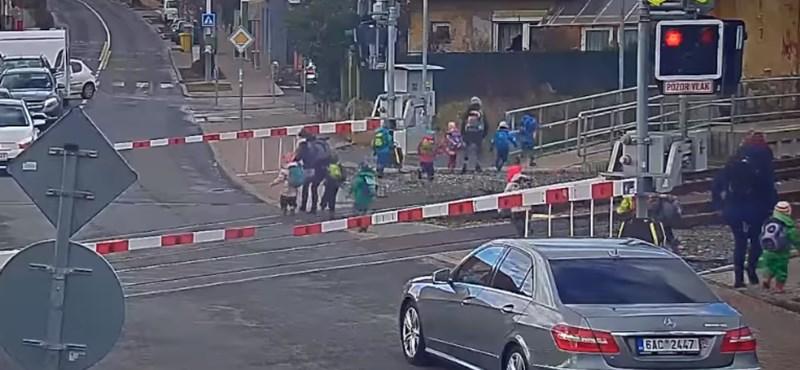 Tilos jelzésénél és lezárt sorompónál vezetik át a síneken az óvodásokat – videó