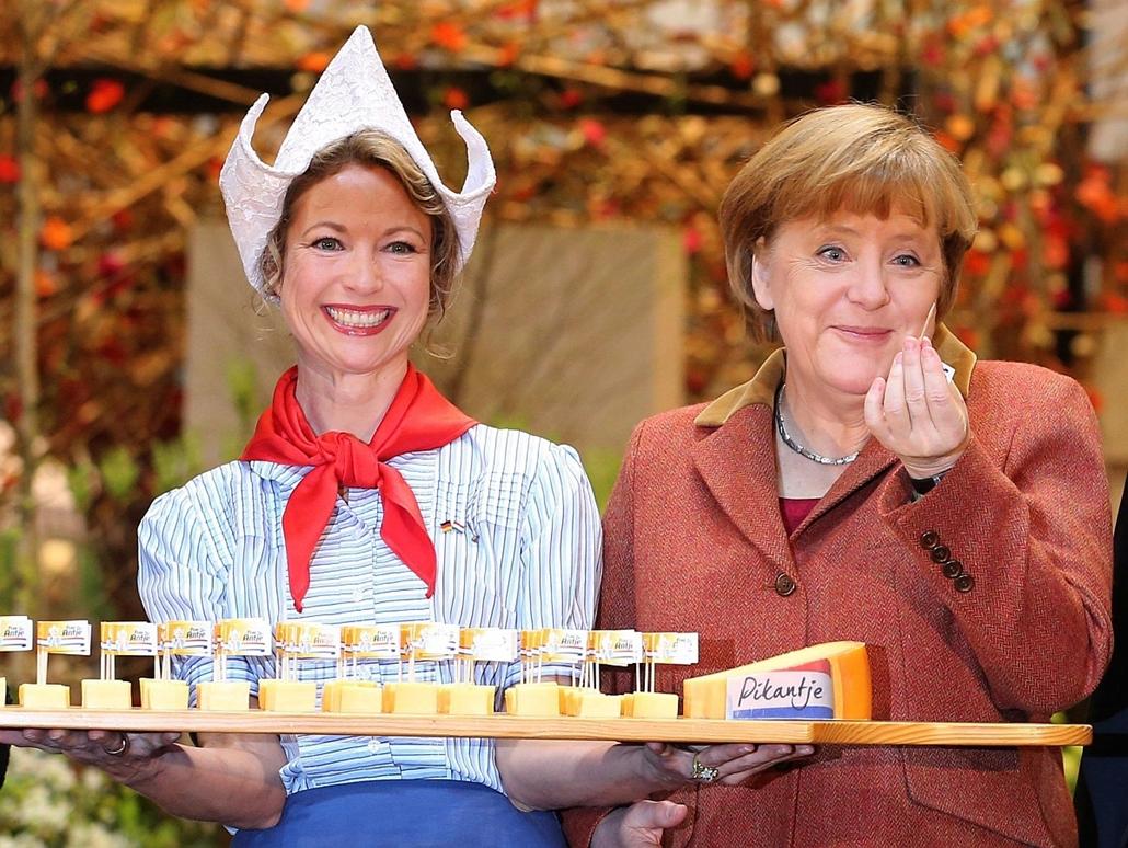 Megnyílt a berlini Zöld Hét mezőgazdasági vásár - Angela Merkel német kancellár (j) megkóstol egy falat sajtot a Zöld Hét mezőgazdasági, élelmiszeripari és kertészeti vásár megnyitóján