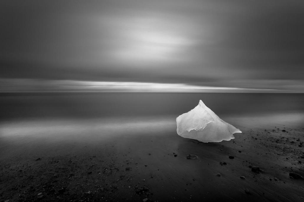 'Honorable mention', 'temészet' kategória - Izland, a Jökulsárlón lagúnától keletre. négy perces expozícióval készült kép egy, a Breiðamerkurjökull gleccserről levált jégdarabról, A világos sáv egy fejlámpával megvilágított partrészlet. - NatGeonagy