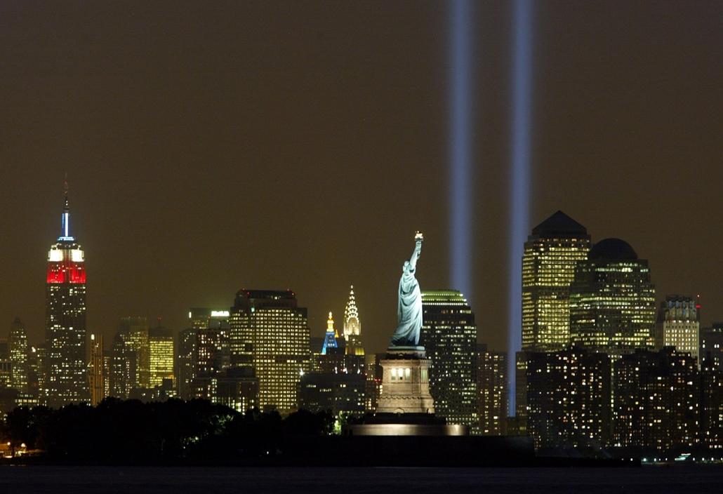 afp.03.09.11. Fénycsóvák fénylenek az éjszakai égbolton Manhattan felett, háttérben a Szabadság szoborral. Három évvel a terrortámadás után így emlékeznek az áldozatokra.