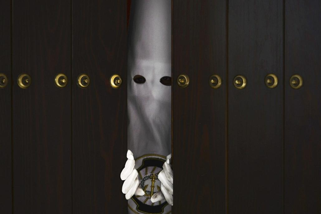 epa. hét képei - Córdoba, 2014.04.16. Spanyolország, húsvét - Córdoba, 2014. április 16. A Béke és Remény keresztény testvériség egyik csuklyás tagja kinéz egy templom ajtaján, mielőtt részt vesz a nagyheti körmeneten a dél-spanyolországi Córdoba egyik te