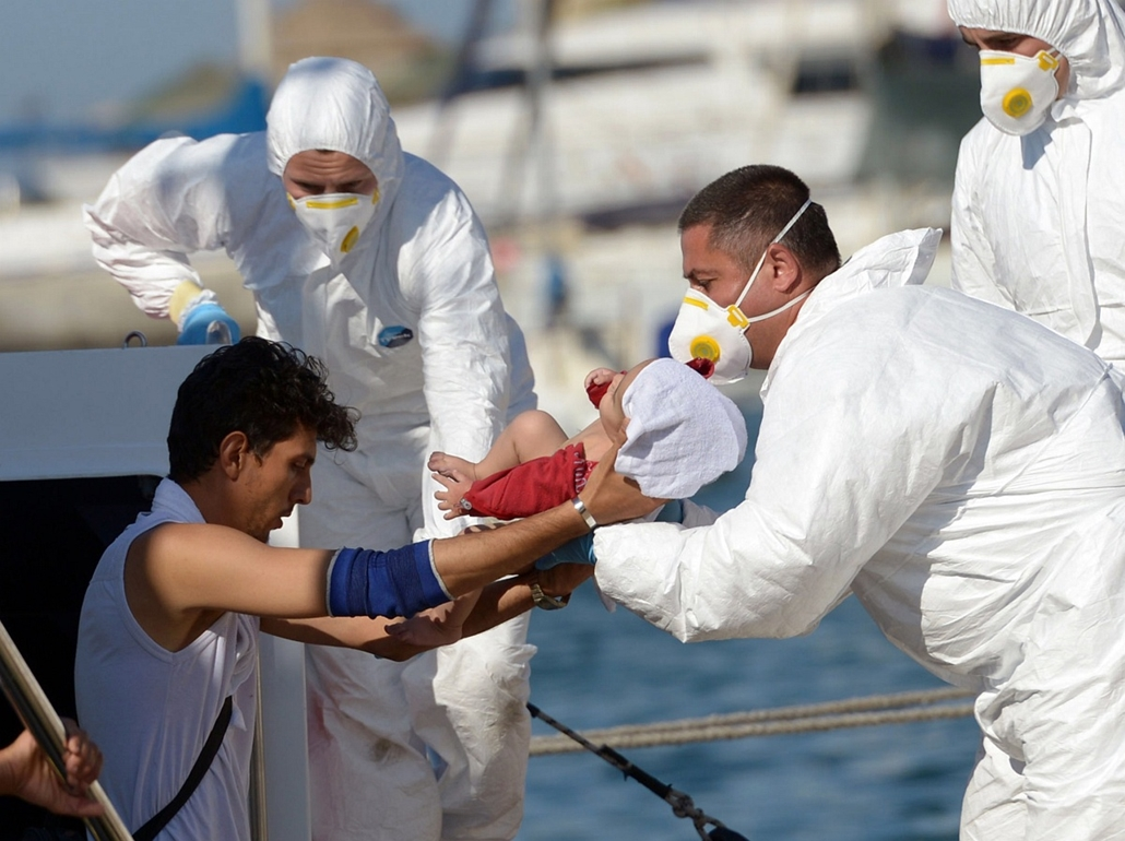afp. hajóval érkező menekültek, migránsok, - Floriana, Málta, 2014.08.28. A migrant disembarks with his baby from a boat of the Armed Forces of Malta (AMF) after arriving at the Haywharf maritime base, in Floriana, Malta, on August 28, 2014. The group of