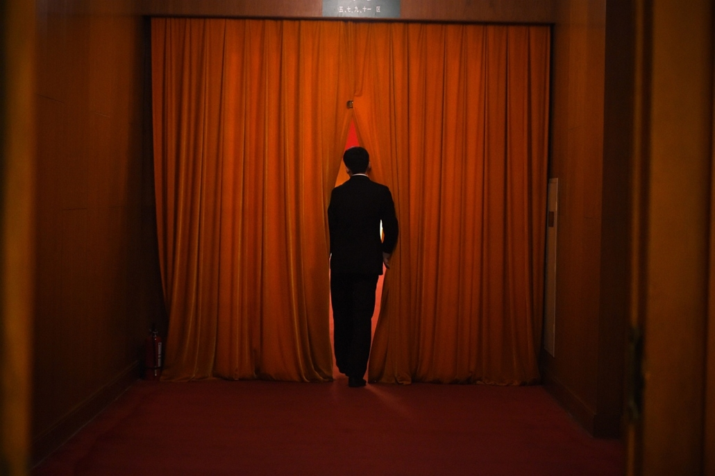 afp. Peking, Kína, 2015.03.12. nemzeti népi kongresszus - A security guard watches through the curtain during the 3rd plenary session of the third session of the 12th National People's Congress at the Great Hall of the People in Beijing on March 12, 2015.