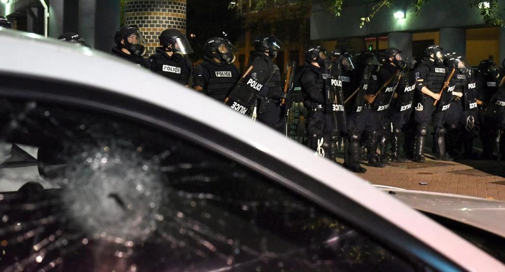 mti.16.09.22. - Bezúzott autóablak rohamrendőri sorfal előterében a rendőri túlkapásokat ellenző, rendbontássá fajult tiltakozáson az Észak-Karolina állambeli Charlotte-ban 2016. szeptember 21-én. A rendőrség könnygázt és gumilövedékeket vetett be a tömeg