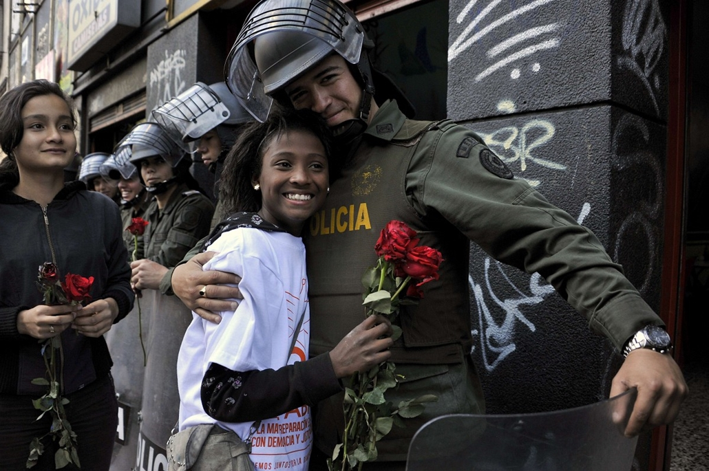 afp.  rendőr, aktivista, ünnep, rózsa, Bogotá, Kolumbia - A riot policeman hugs an activist who gave him a rose during the National Day of Remembrance and Solidarity with Victims of the Armed Conflict, in Bogota, Colombia on April 9, 2014. In Colombia, th