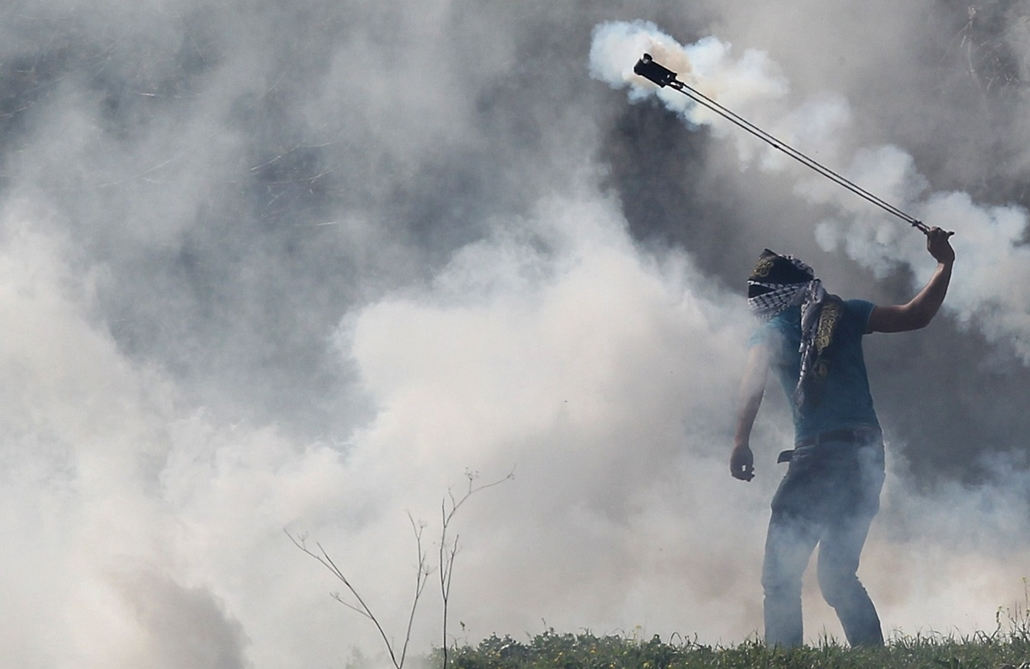 afp. palesztin tiltakozó 2015.03.10. Betunia, A masked Palestinian protester hurls away a tear gas canister fired by Israeli severity forces during clashes following a demonstration by students from Birzeit University near Ramallah against the incarcerati