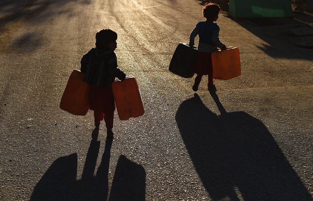 afp. hét képei - Kabul, Afganizstán, 2014.12.09. Afghan children carry cans of water in Kabul on December 9, 2014. Afghanistan is a mountainous country in a dry part of the world which experiences extremes of climate and weather, with winter cold and snow