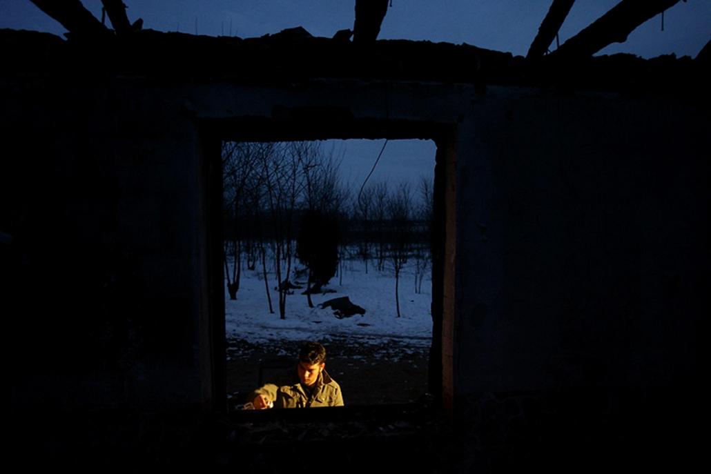 Hír-eseményfotó (egyedi) - III. díj: Máté Péter (Magyar Nemzet):Gyász - Tatárszentgyörgy, 2009. február 24. Egy megemlékező gyertyát gyújt a kiégett ház ablakában, ahol egy roma kisfiút és édesapját agyonlőtték.