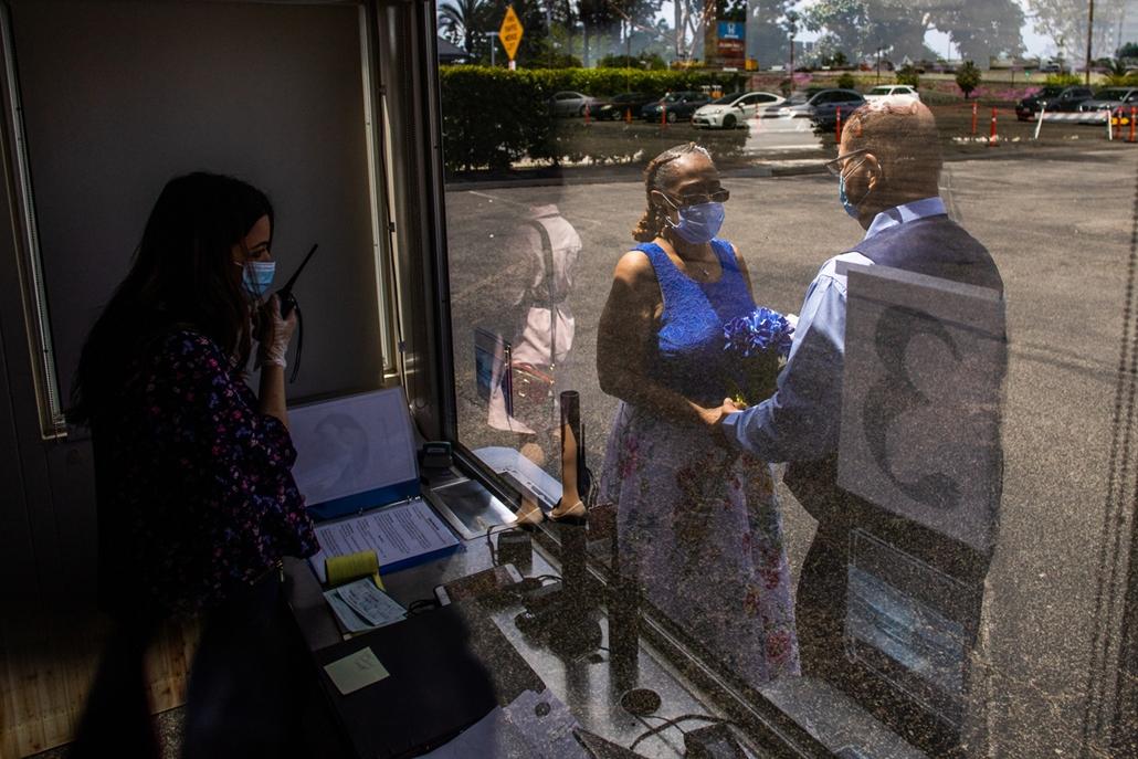 NAGYÍTÁS ÉV KÉPEI április Clerk Recorder Erika Patronas (L) officiates the wedding ceremony of Natasha (C) and Michael Davis at the Honda Center parking lot on April 21, 2020 in Anaheim, California. - The County of Orange Clerk Recorder employees implemen