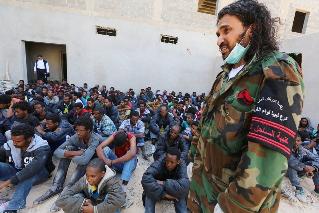 afp. hajóval érkező menekültek, migránsok, - Zawiya, Líbia, 2014.05.12. A member of the Libyan security forces stands guard near some 340 illegal migrants who were rescued by the Libyan navy off the coast of the western town of Sabratha when their boat be
