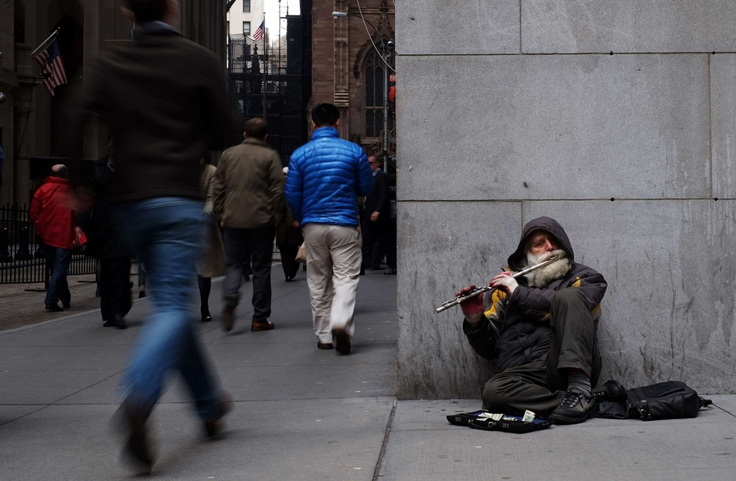 afp. hét képe - New York, USA, zenész, koldus, A musician plays a flute sitting on the footpath next to New York Stock Exchange (NYSE) building on March 11, 2015 in New York.